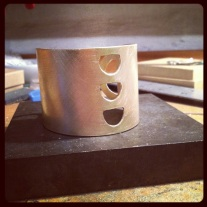 Brass cuff in production.
